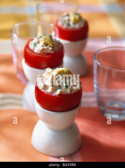 Tomatoes in egg cups stuffed with crab - Stock Image