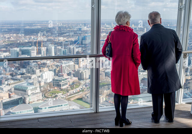 An elderly couple look out over London from the viewing gallery of The Shard in London, UK - Stock Image