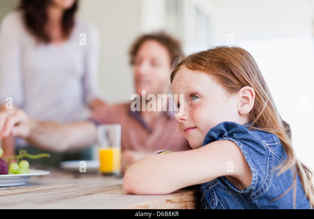 Girl sitting at breakfast table - Stock Image