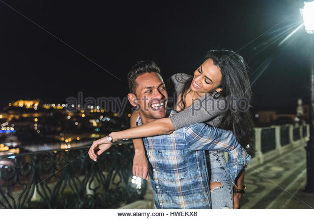Couple in city at night, fooling around, man carrying woman on back, Lisbon, Portugal - Stock-Bilder