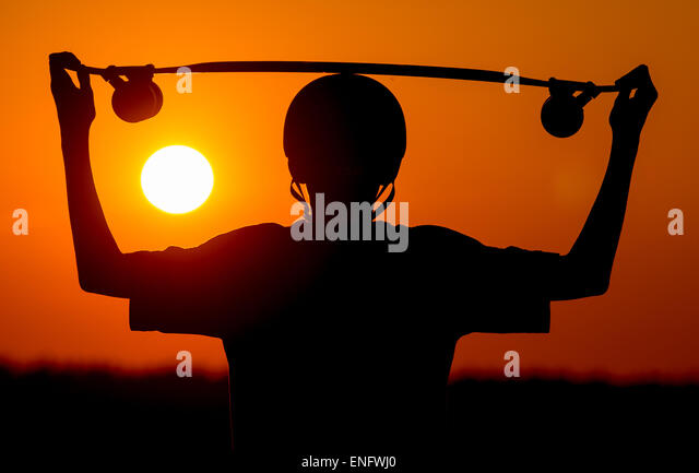 ILLUSTRATION - A boy and his longboard at sunset on a bike path near Sieversdorf in the Oder-Spree district, Brandenburg, - Stock-Bilder