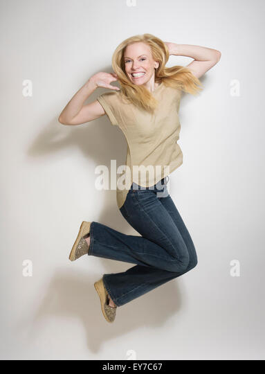 Portrait of mid-adult woman jumping - Stock Image