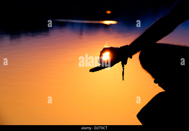 Sunrise silhouette of a mans hand whilst meditating on rocks at an Indian lake. Andhra Pradesh, India - Stock-Bilder