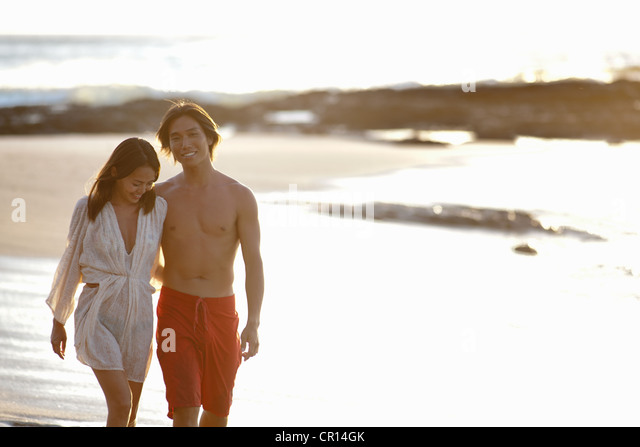 Couple walking together on beach - Stock Image