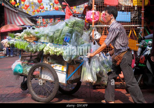 Bangkok Thailand Samphanthawong Chinatown Mangkon shopping market marketplace Asian man cart produce vegetables - Stock Image