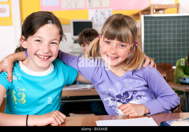 portrait of two young girls in classroom embracing - Stock Image