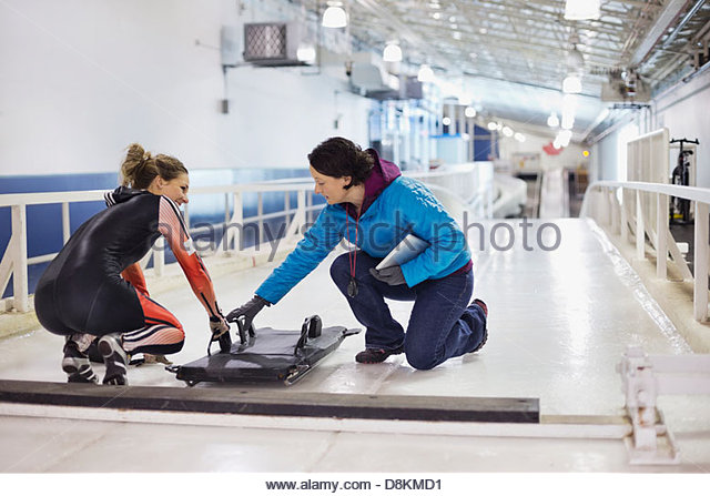 Female coach explaining technique to skeleton athlete - Stock Image