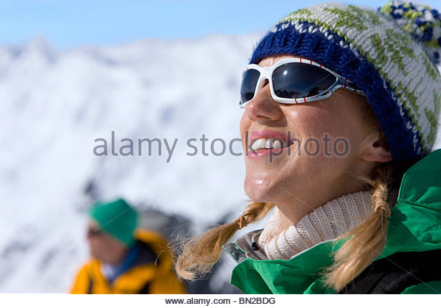 Happy woman enjoying sunshine on snowy mountain - Stock Image