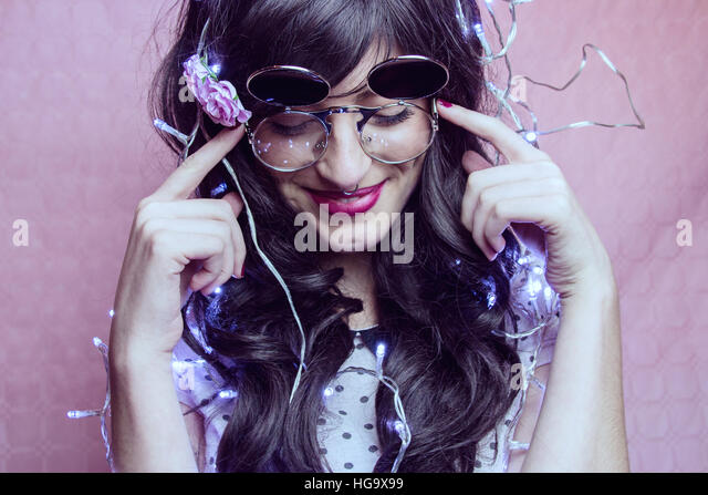 Young woman enjoying a party wearing christmas lights - Stock Image