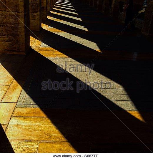 Pillars and sunlight patterns on yellow stone. - Stock Image