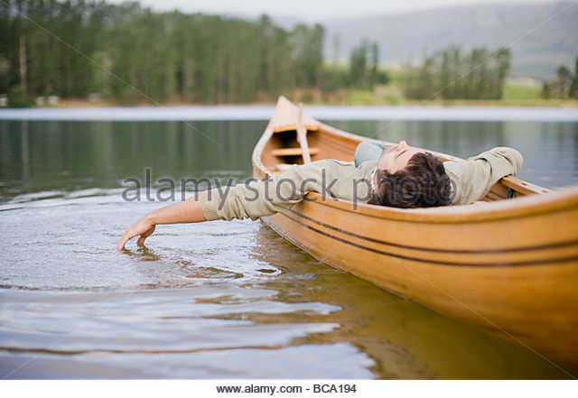 Man reclining in canoe on lake - Stock Image