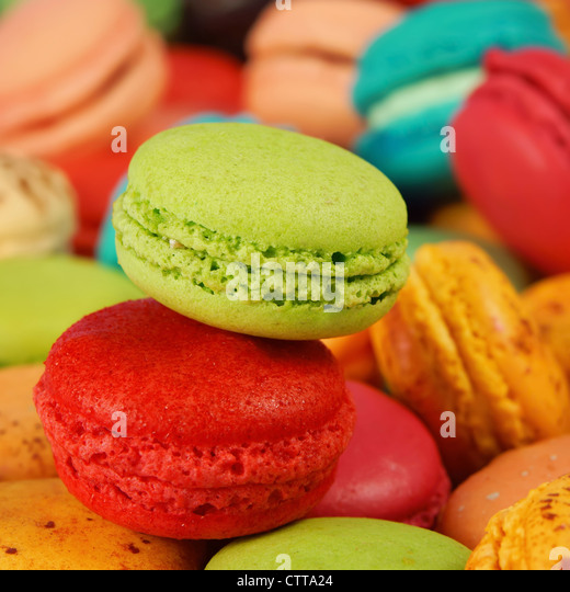 strawberry and pistachio macaroons on an assortment of colorful macaroons - Stock Image