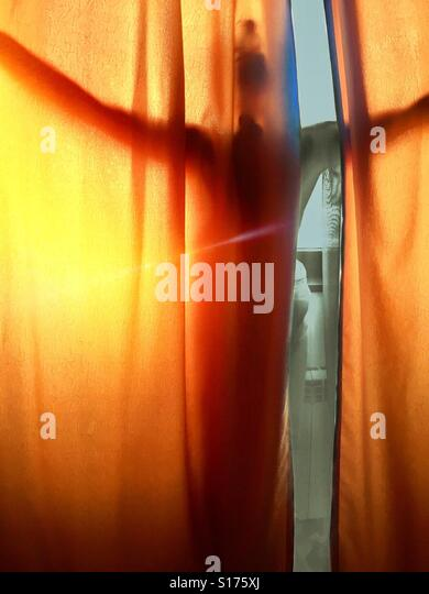 Woman taking in the view behind a curtain - Stock-Bilder