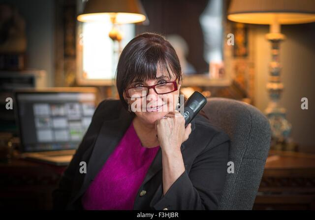 Portrait of senior woman in office, using telephone - Stock Image