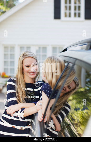 Mother talking to daughter in car window - Stock Image