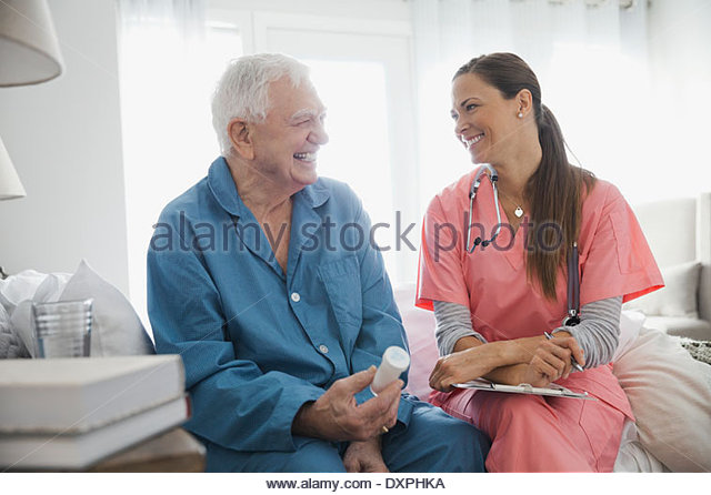 Home care nurse sitting with senior patient - Stock Image