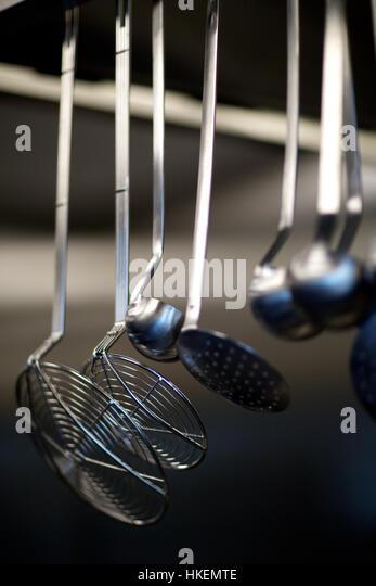 strainers on kitchen rack. kitchen, clean, steel, colander. - Stock Image