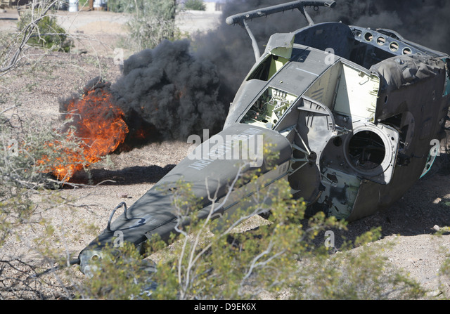 Black smoke rises to the air from a simulated wreckage of a downed UH-1N Huey. - Stock Image