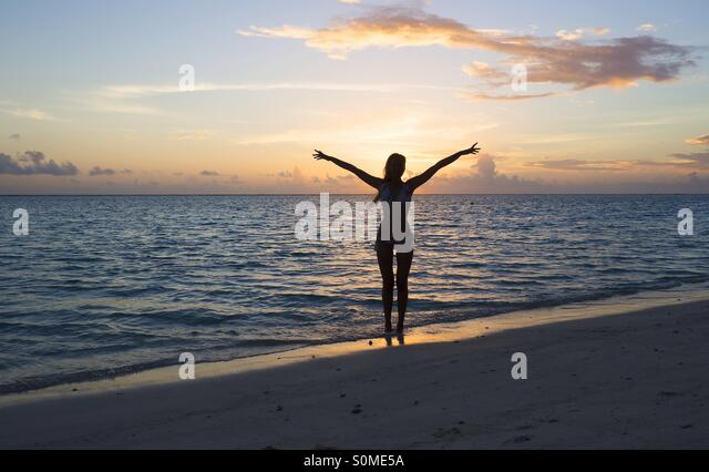 A woman is posing on a beach in the Maldives at sunset - Stock Image