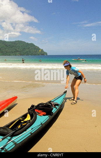 Woman kayaker preparing to launch kayak from beach in the Caribbean on the island of Trinidad. - Stock Image
