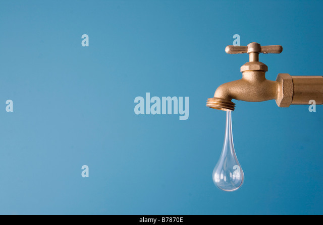 giant drop of water drips from faucet - Stock Image