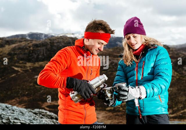 Young couple taking a break from hiking, having hot drink, Honister Slate Mine, Keswick, Lake District, Cumbria, - Stock Image