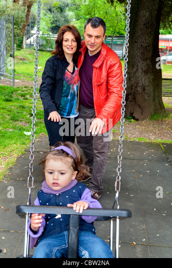 Parents pushing daughter on a swing - Stock Image