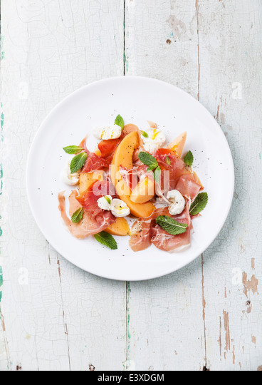 Melon and prosciutto ham salad with Mozzarella and mint leaves - Stock Image