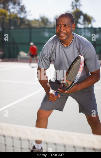 Older man playing tennis on court - Stock Image