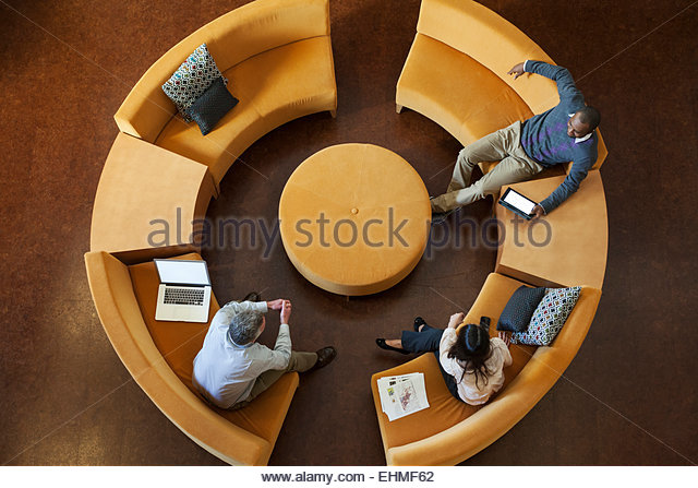 Overhead view of business people talking on circular sofa - Stock Image