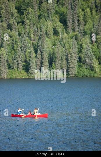 Family paddles a canoe together on Byers Lake, Summer, Denali State Park, Southcentral Alaska - Stock Image