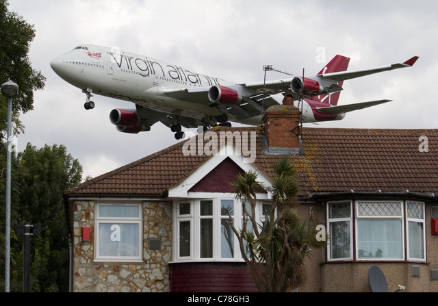 Low flying aircraft Heathrow airport approachVirgin atlantic, noise pollution with residential housing - Stock Image