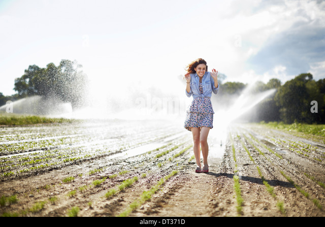 A young woman in denim jacket standing in a field irrigation sprinklers working in the background - Stock-Bilder