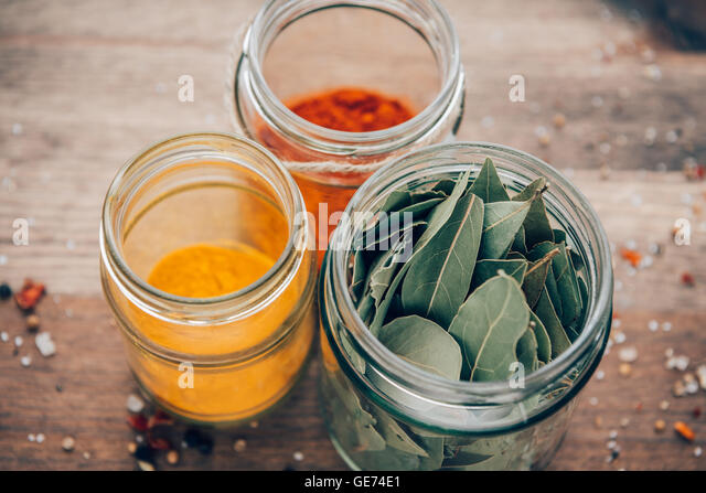 Bay leaves, turmeric and paprika powder in jars on a wooden table. - Stock Image