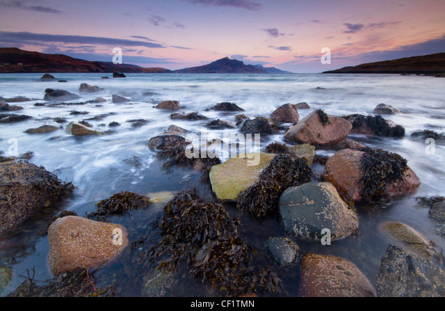 The sea lapping around rocks on the shore at Balmeanach a quiet crofting township near Dunvegan on the Isle of Skye. - Stock-Bilder