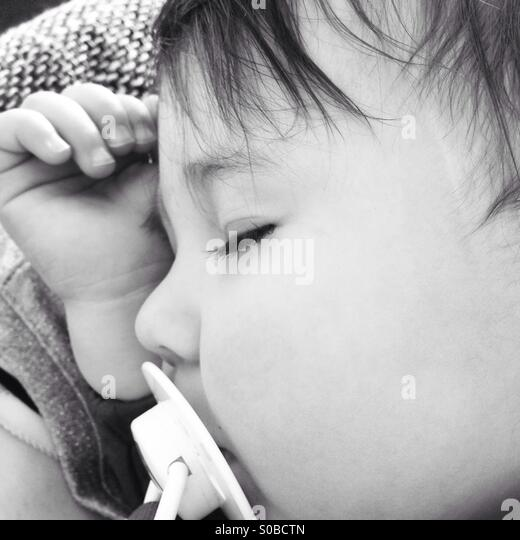 Small baby girl sleeping with soother in black and white - Stock-Bilder