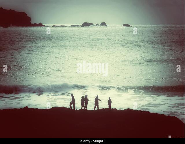 Five people silhouetted against an ocean with rolling waves. - Stock Image