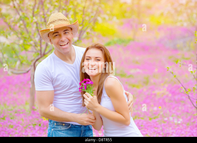 Happy smiling couple having fun in summer park, relaxation outdoors on pink floral glade, romance and love concept - Stock Image