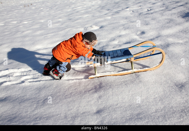 Child pushing a sledge on the snow, Jerzens, Austria - Stock Image