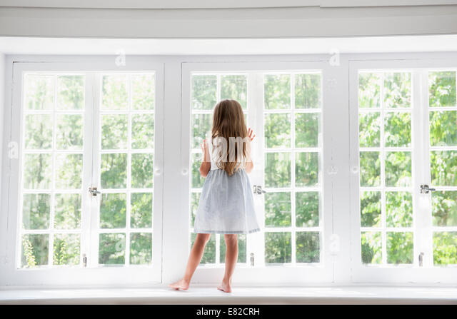 A child standing at a window looking out. - Stock Image