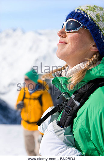 Happy woman with backpack enjoying sunshine on snowy mountain - Stock Image