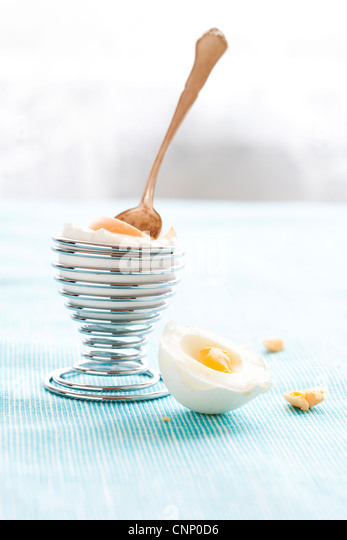 Close-up of a hard-boiled egg in a silver spiral eggcup - Stock Image