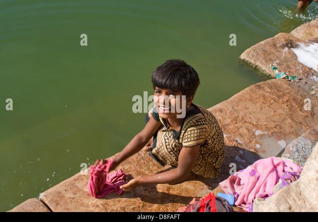 Asien, Indien, Karnataka, Banashankari, Maedchen waescht Kinderkleidung - Stock-Bilder