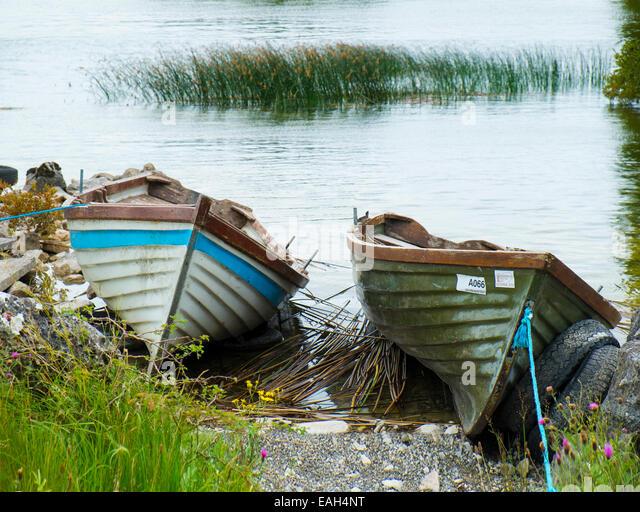 Lake angling boats drawn up on the lake shore at Lough Corrib, County Galway, Ireland - Stock Image