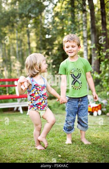 Sweden, Narke, Hallsberg, Boy (4-5) and girl (2-3) holding hands - Stock Image
