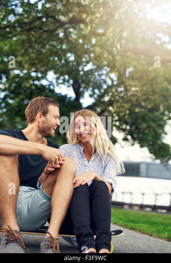 Couple fooling around on a skateboard, big city couple - Stock Image