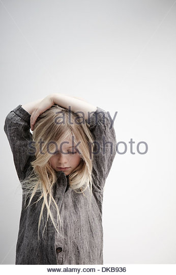 Portrait of girl with hands on head - Stock Image