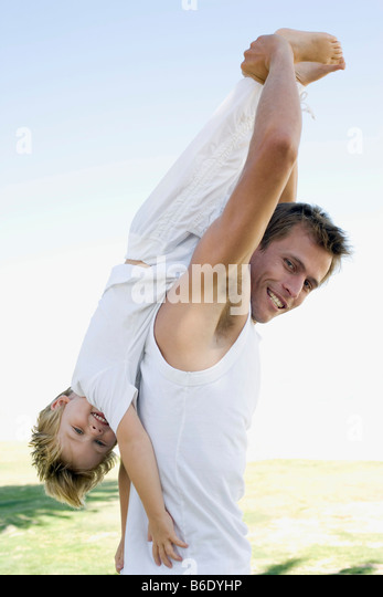 Father and son. Father playfully lifting his son upside down. - Stock Image