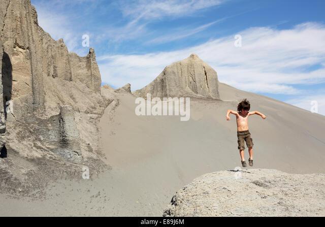Boy jumping on sand dunes - Stock Image