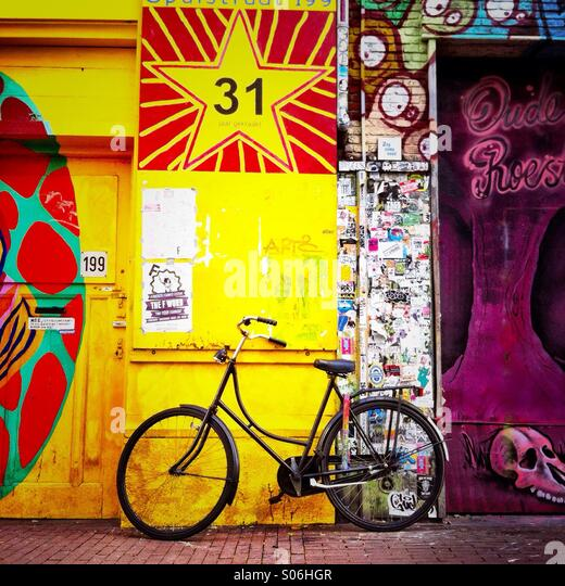 A bike leaning against a wall with graffiti on it. Amsterdam the Netherlands. Europe. - Stock Image